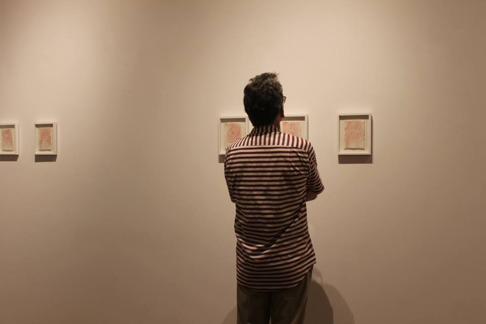 An exhibit guest contemplating on the story of Louie's Visual Diary - Red Series