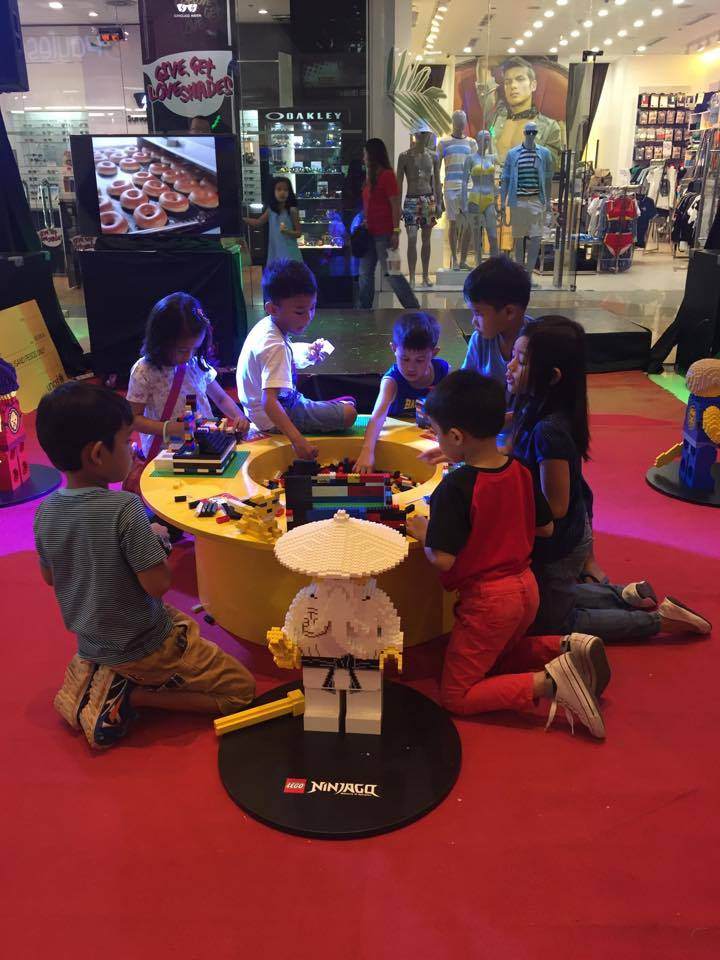Kids building with bricks outside the Lego Store.